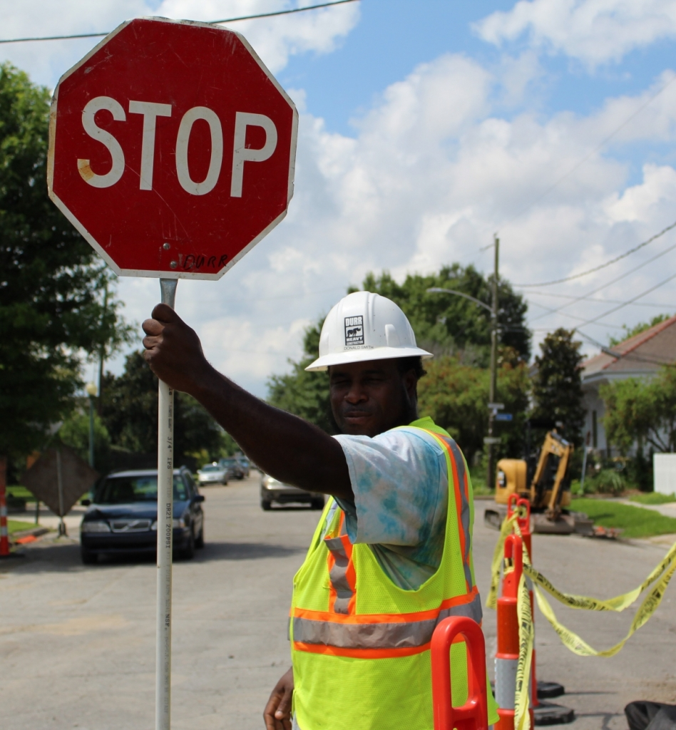 a construction worker flags traffic with a stop sign