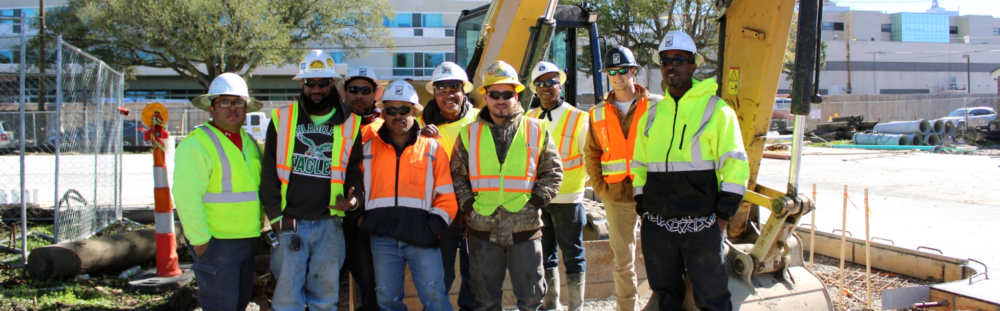 A Durr crew poses in front of an excavator