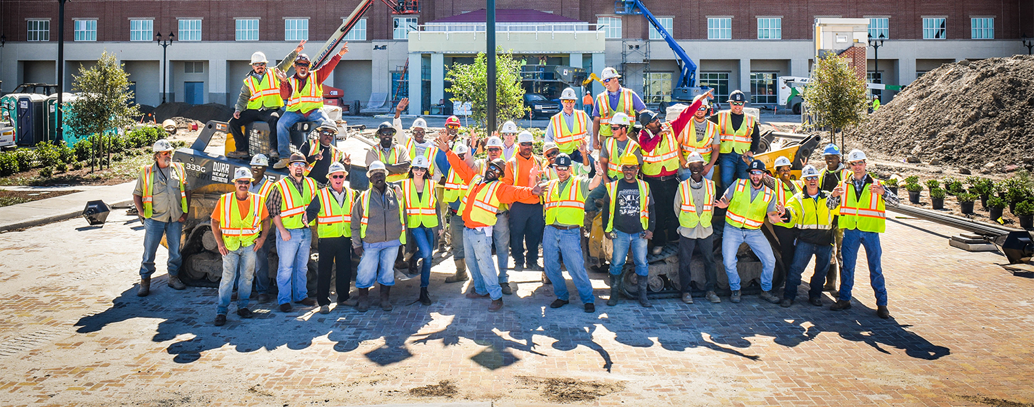 A large group of Durr employees posing in front of a building