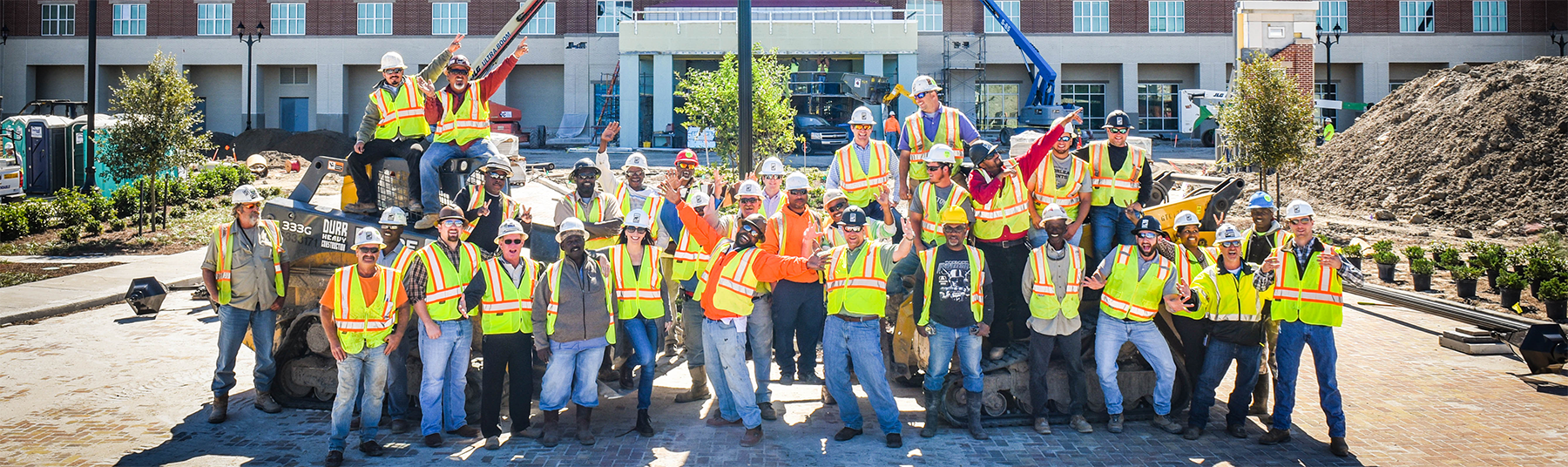 a group shot of Durr employees at a project site with their hands raised in the air for celebration