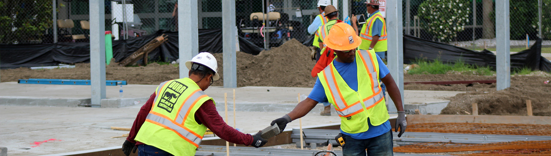A worker passes a brick to another crew member