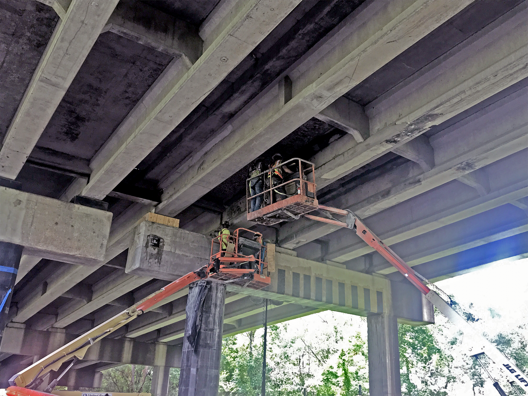 workers on lifts underneath a bridge