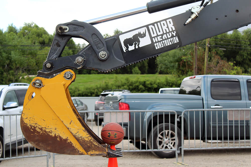 Excavator picking up a basketball