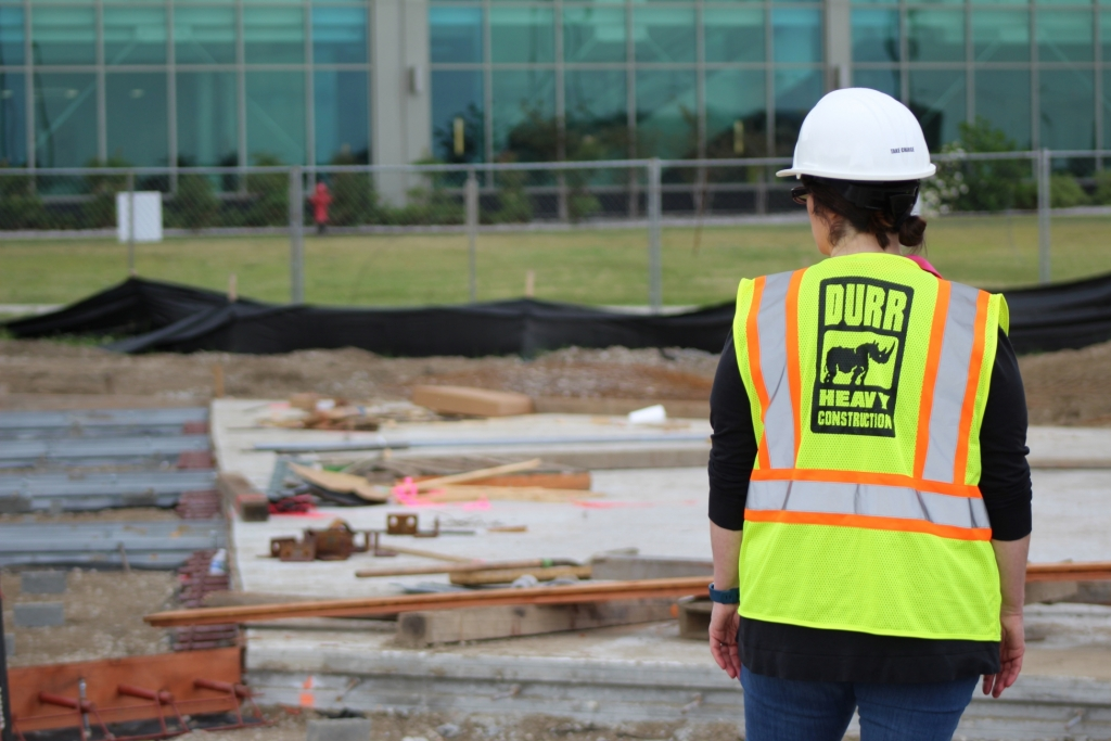 a durr worker wearing a safety vest with her back to the camera