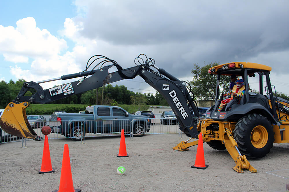 An excavator picking up a basketball off of a cone