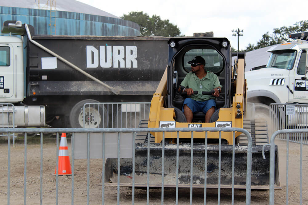 A worker driving a skidsteer