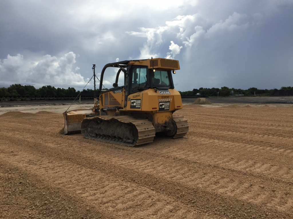 a dozer pushes sand at a job site