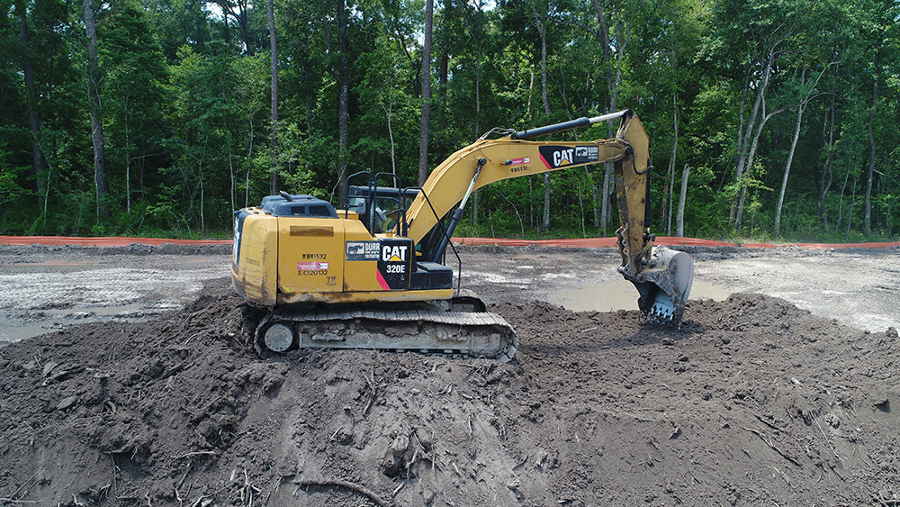 an excavator sits on a large pile of dirt