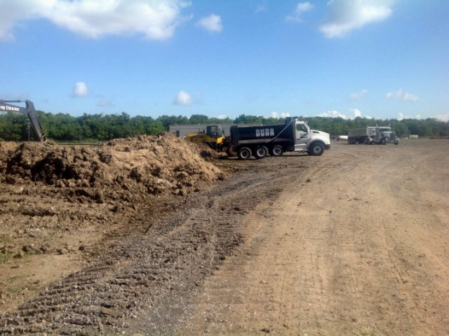 a dump truck lines up next to a pile of dirt