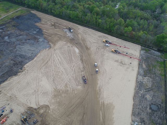 an overhead shot of a job site with multiple pieces of equipment driving around