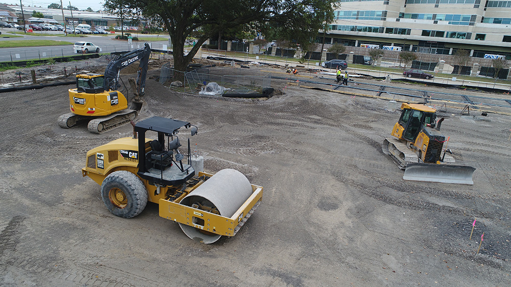 an excavator, a roller, and a dozer parked at a jobsite