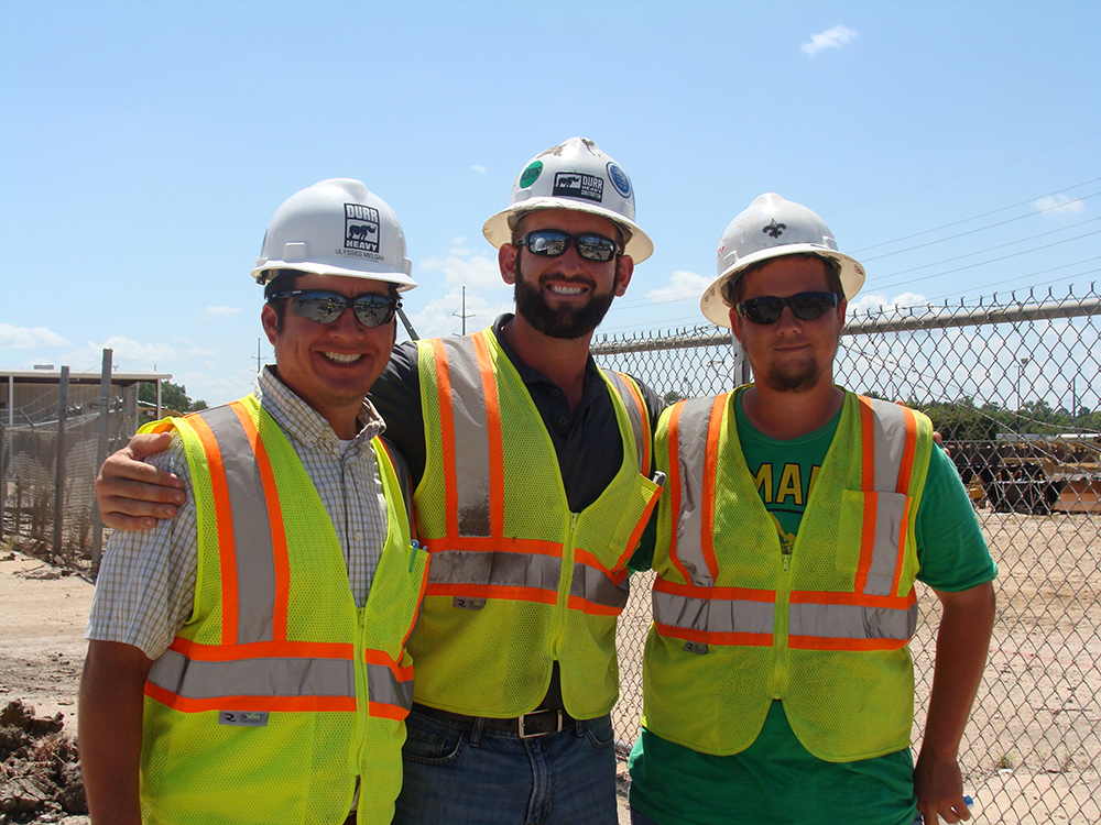 three workers smiling at the camera weairng hard hats and vests