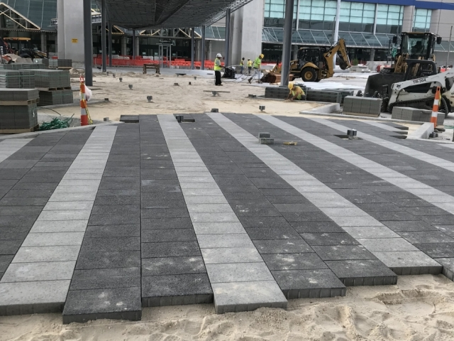 construction workers lay down pavers