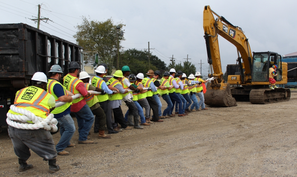 workers jokingly play tug of war involving a giant piece of rope with an excavator