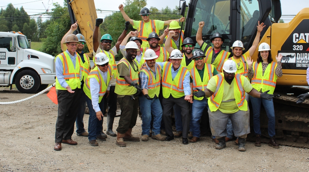 a group of workers pose with their hands up in the air