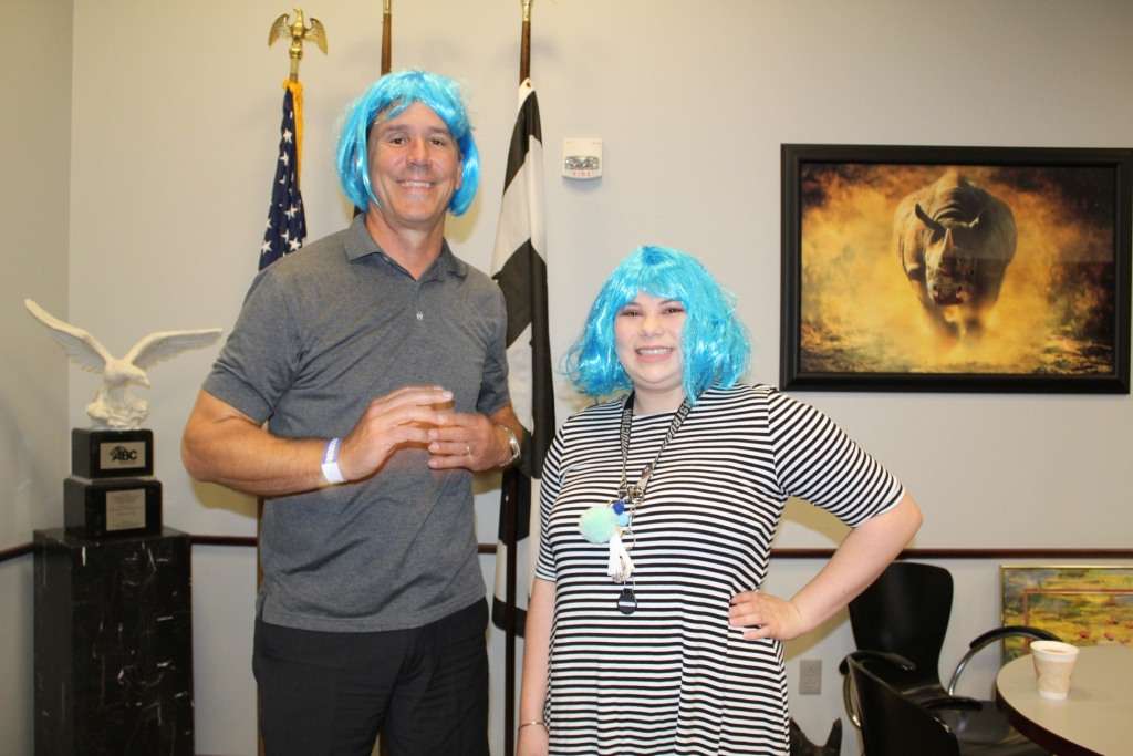 two workers wearing blue wigs pose for the camera