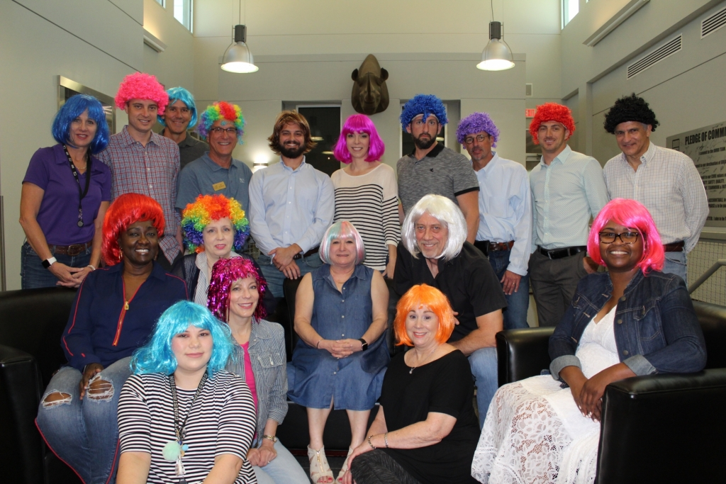 employees all have on colorful wigs as they pose for the camera in a group