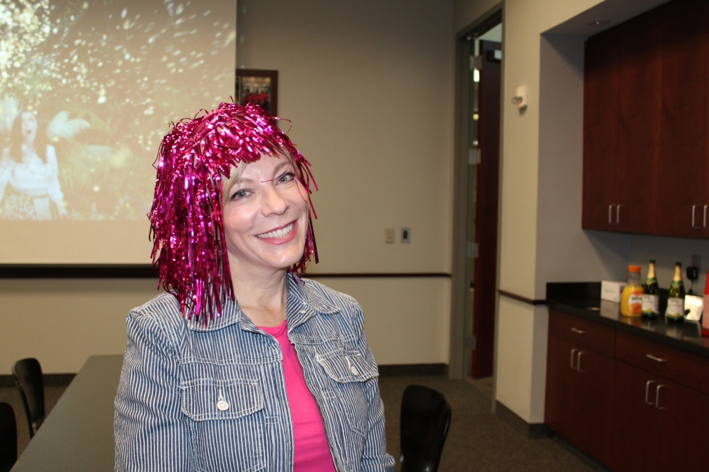 a worker in a pink wig smiles