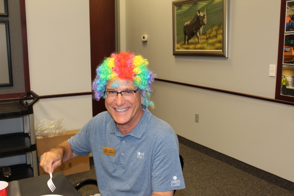 a worker in a rainbow wig smiles