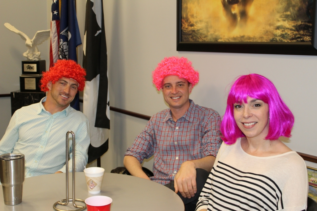 a group of workers in colorful wigs smile at the camera