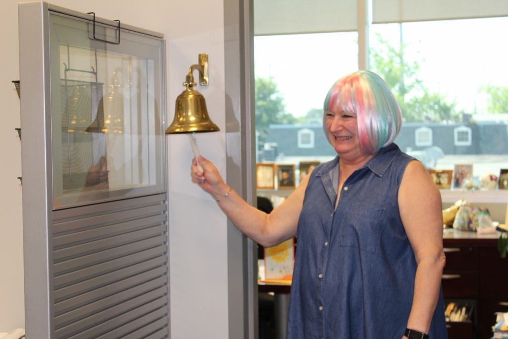 Jan, wearing a colorful wig, rings a bell signifying that she has beaten cancer