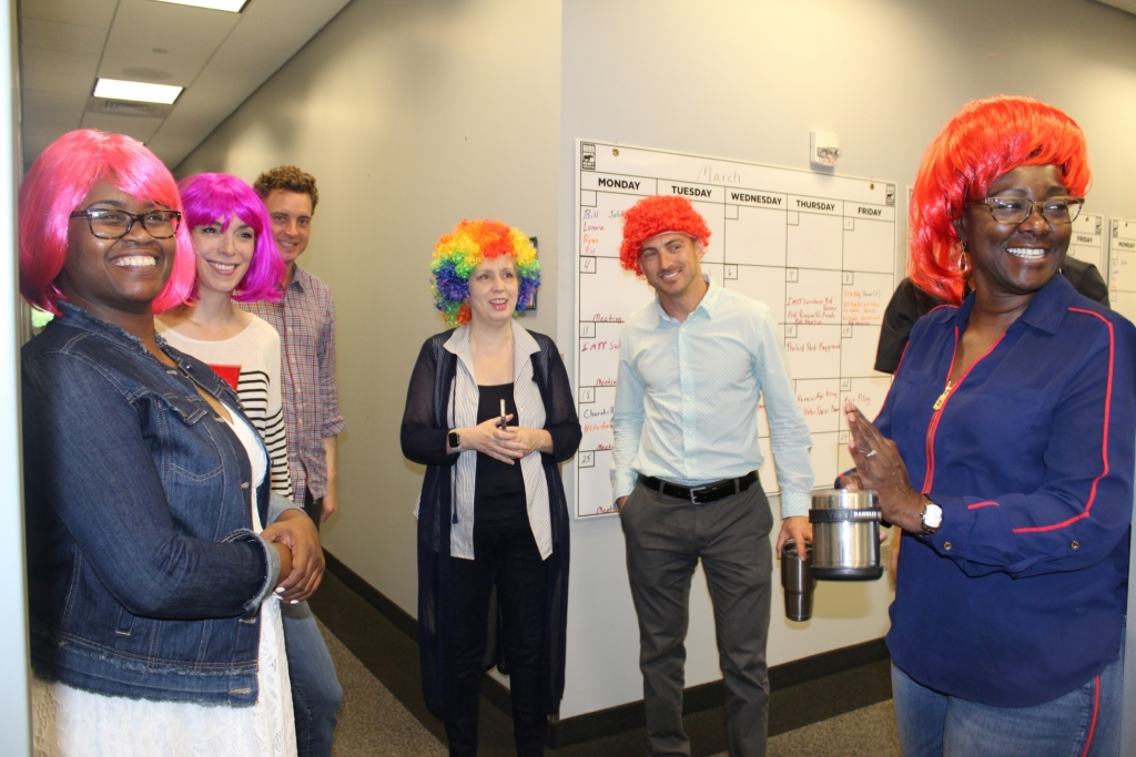 a group of workers in colorful wigs smile as they clap