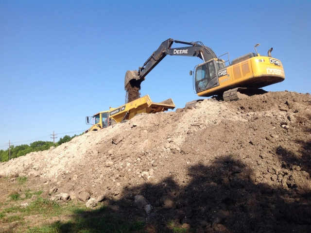 an excavator, on top of a hill, loads a large truck with dirt