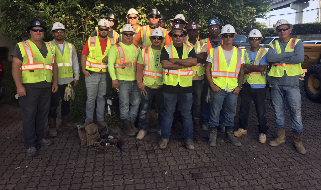 a group of workers wearing hard hats and vests pose for the camera