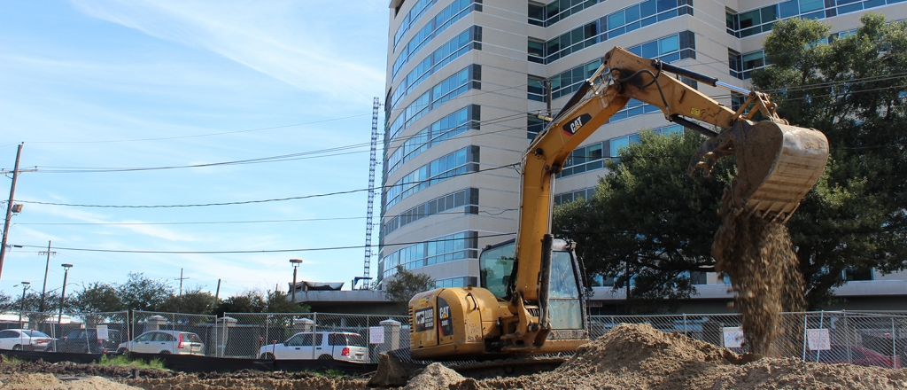 an excavator drops dirt onto a project site