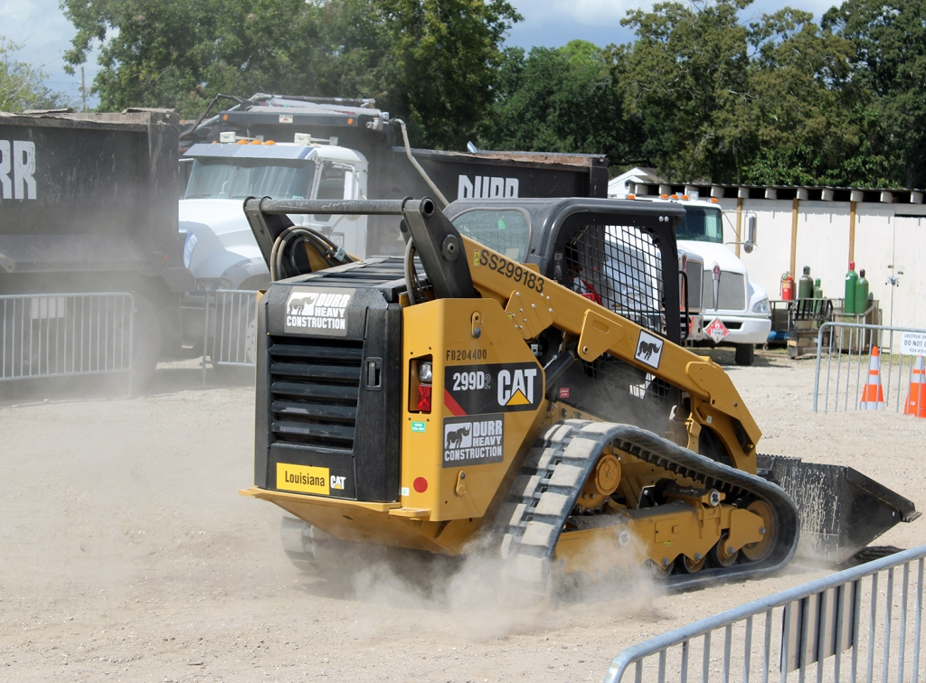 a skidsteer kicks up dirt as it moves