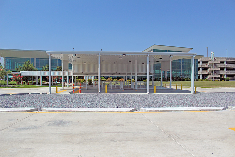 a wide shot of the bus turn-around canopy with an airport terminal in the background