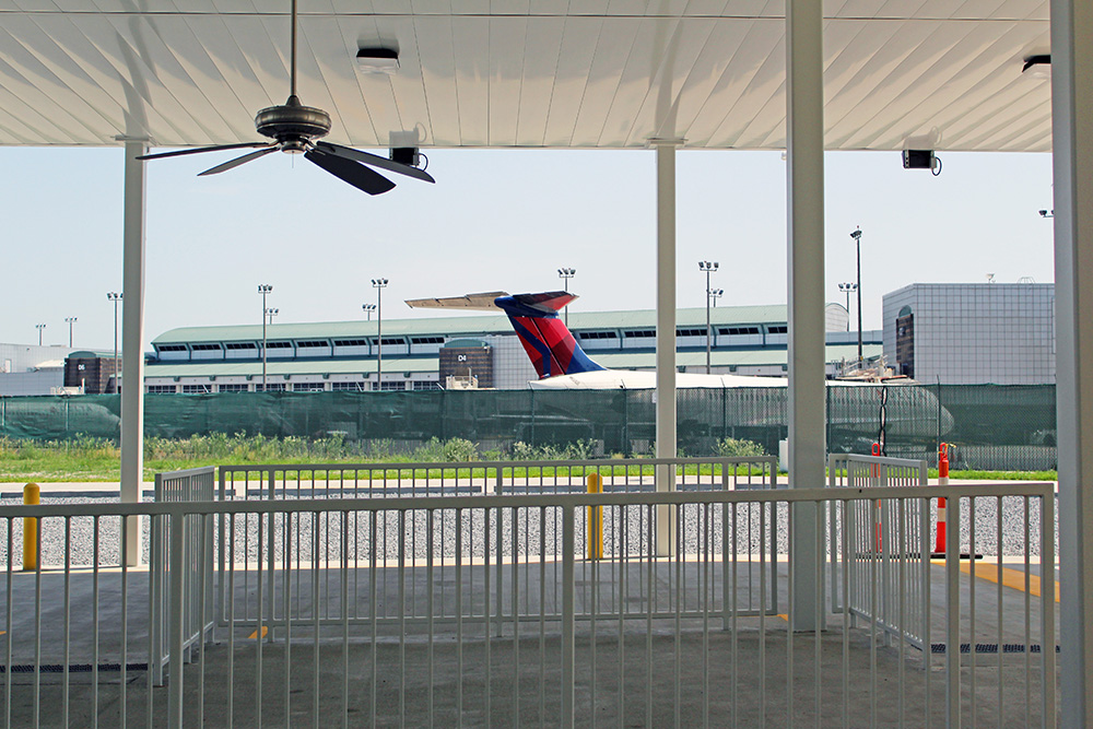 underneath the canopy shelter. A parked plane can be seen in the background