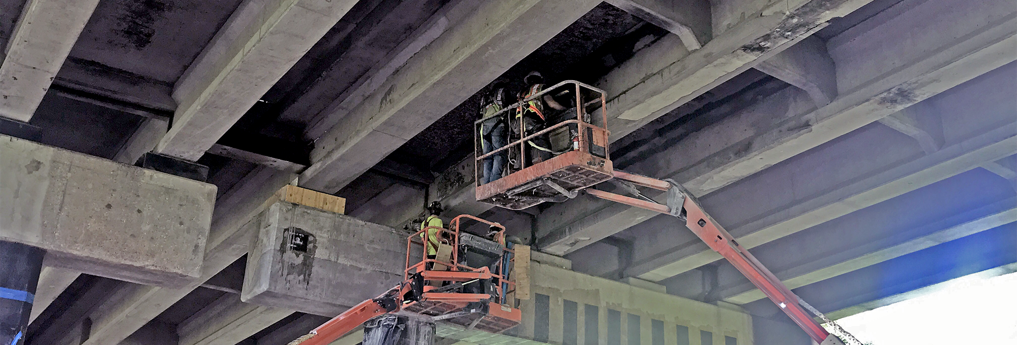Workers stand on a lift underneath the bridge